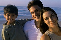 Portrait of parents and their son smiling on the beach
