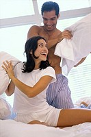 Young couple having a pillow fight in bed