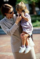 Close-up of a mother carrying her daughter talking on a mobile phone