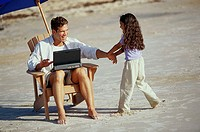 Father working on a laptop with his daughter pulling his hand on the beach