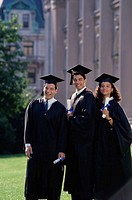 Two male graduates with a female graduate holding diplomas