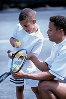 Side profile of a father teaching his son to play tennis