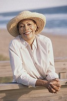 Portrait of a senior woman leaning against a railing near the beach
