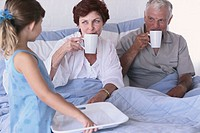 Girl Bringing Coffee to Grandparents in Bed