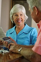 Senior man using a calculator with a senior woman sitting beside him
