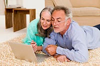 Mature couple in living room, lying on floor with laptop