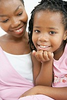 Girl (5-7) sitting with mother, smiling, portrait