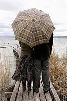 Couple on jetty with umbrella, rear view