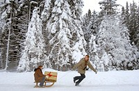 Young man pulling woman on sledge with Christmas gift