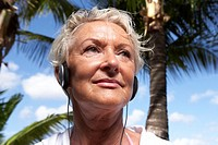 Senior woman listening to headphones, close up, low angle