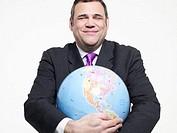 Mature businessman embracing globe, smiling, close-up