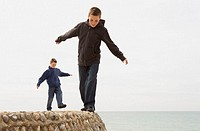 Two boys (11-13) walking on beach wall