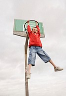 Boy (11-13) hanging from basket ball hoop, shouting, low angle view