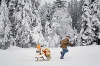 Man pulling woman holding present on sledge, side view
