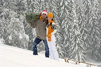 Couple in snow, man carrying christmas tree, woman pulling sledge