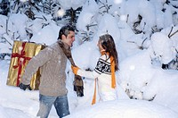 Young couple standing in snow, man holding gift, side view