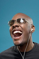 Young man listening to music, laughing, close-up