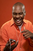 Young man listening to mp3 player, laughing, close-up