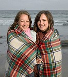 Two young women on beach wrapped in blanket, smiling, portrait