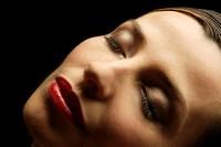 Woman tilting head back, eyes closed, close-up