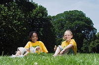 Two girls (8-10) sitting on grass with flowers, smiling