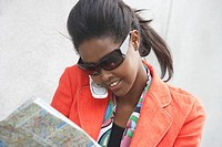 Young woman looking at map and talking on cell phone