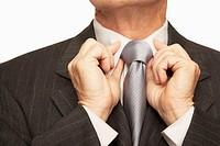 Senior businessman adjusting tie, mid section