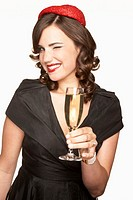 Young woman holding glass of champagne, winking, portrait