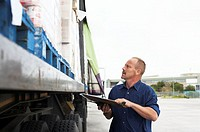 Man holding clipboard checking lorry loaded with canned produce