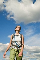 Young woman hiking, wearing backpack, low angle view