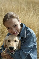Girl (9-11) hugging yellow Labrador retriever puppy in field