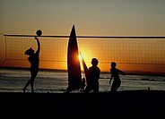 Silhouette of people playing volleyball on the beach at sunset with sailboat in background