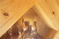 Two women sitting inside sauna in Sweden