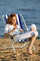 Young woman sitting in deck chair on beach, looking away