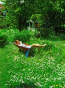 Girl resting in wheelbarrow in yard filled with bellis flowers