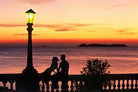 Couple on wall at sunset under lamp in Colonia del Sacramento in Uruguay