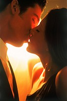 Couple kissing in soft bedroom light