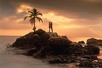 Couple on rocky point with one palm tree on Mahe Island in Seychelles at sunset