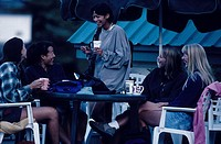 Five women laughing together as they have coffee in a casual outdoors cafe
