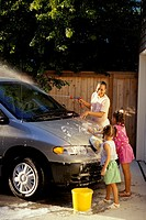 African-American mother and her two young daughters wash the family mini-van together in the driveway of their home