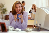 Female executive sits at her desk by her computer and holds a blue mug with both hands