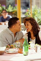Hispanic man and Caucasian woman smiling at each other while having lunch at an outdoor restaurant