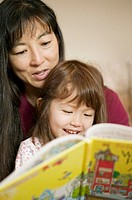 Close-up of mother reading a book to her young daughter both of Asian ethnicity
