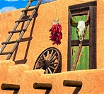 View of the outside of a southwestern style home with red peppers and a longhorn skull hanging next to a wagon wheel and ladder that are leaning up ag...