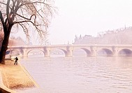 An artist paints a picture of a bridge in misty light as he stands on the quay beside the Seine River in Paris, France