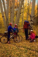 Couple with mountain bikes talking with couple hiking in the woods among fall foliage