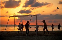 Silhouette of a group of men running and playing soccer on the beach at sunset, Isla Mujeres, Mexico