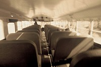 Black and white inside shot of the length of an entire school bus with a few blurred children in the bus