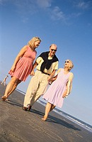 Elderly couple and their adult daughter holding hands while strolling along the beach