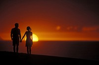 Couple standing hand in hand and looking at each other while they are silhouetted by the setting sun
